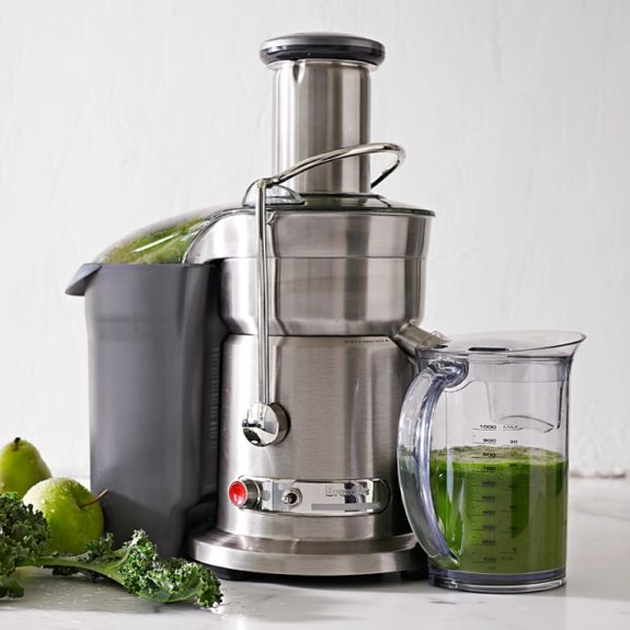 Large juicer with green juice from apples and kale