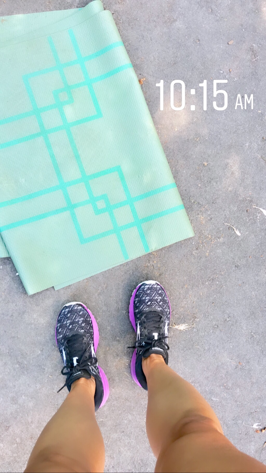 Brooks Running sneakers and a yoga mat on the ground shot from above